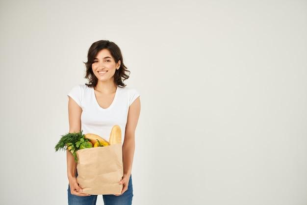陽気なブルネットの白いtシャツの買い物袋の配達