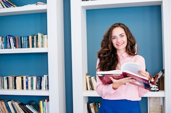 Cheerful brunette with textbook looking at camera