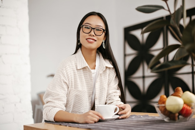 Cheerful brunette woman in eyeglasses, massive earrings and beige jacket smiles and holds cup of coffee