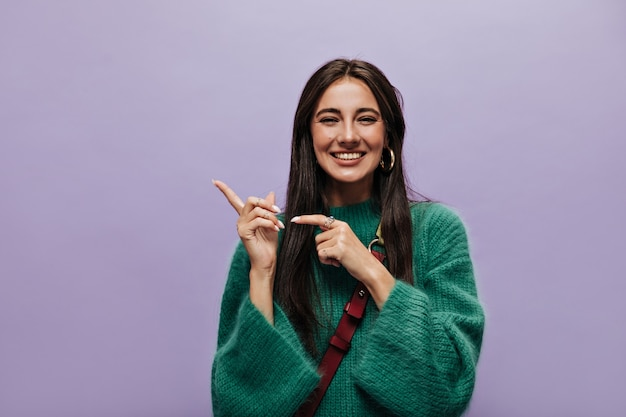 Cheerful brunette woman in green stylish woolen sweater smiles sincerely