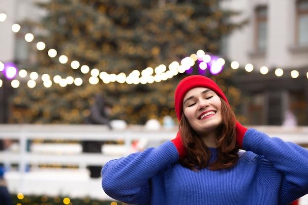 クリスマスフェアで楽しんでいる陽気なブルネットの女性。テキスト用のスペース