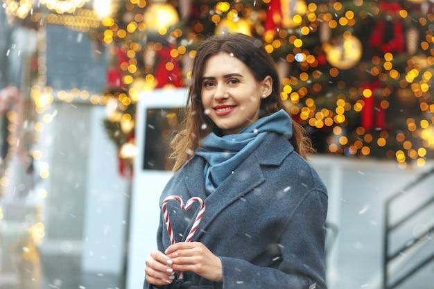 降雪時にハートの形でキャンディーを保持している陽気なブルネットの女性