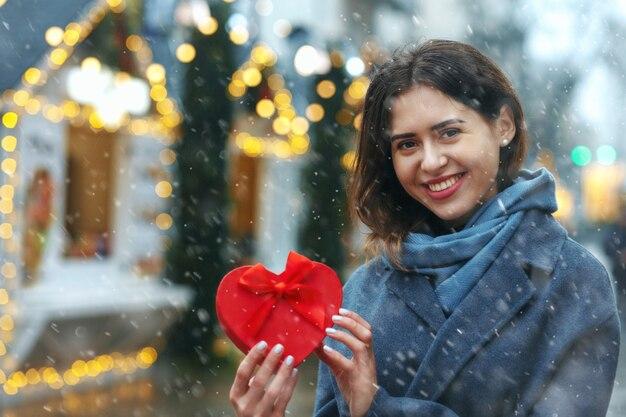 降雪時にクリスマスツリーの近くにギフトボックスを保持している陽気なブルネットの女性。テキスト用のスペース