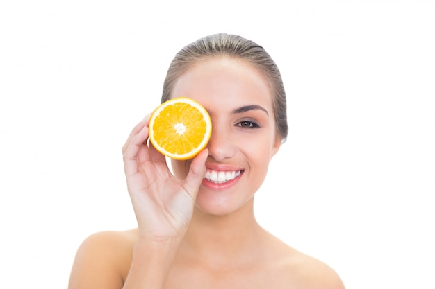 Cheerful brunette woman holding an orange half in front of her eye