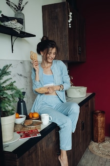 Allegra donna bruna con pasticcini in cucina