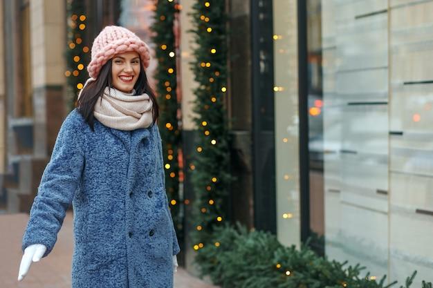 冬を楽しんでコートを着た陽気なブルネットの女性。空きスペース