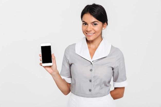 立っている間空白のモバイル画面を示す灰色の制服を着た陽気なブルネットの女性