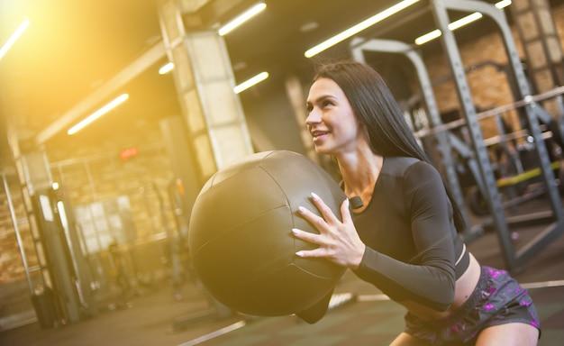Веселая брюнетка женщина в спортивной одежде, упражнения с мячом.