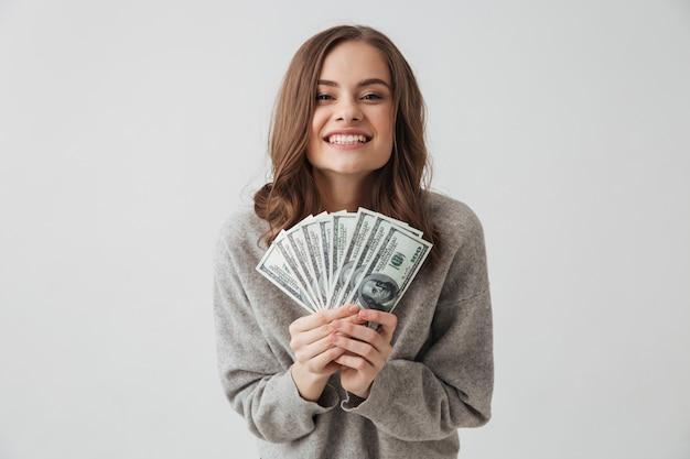 お金を入れているセーターで陽気なブルネットの女性と灰色の壁を喜ぶ