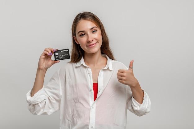 흰 셔츠를 입은 쾌활한 브루네트 여성은 엄지손가락을 치켜들고 흰색 배경 위에 신용카드를 들고 있다
