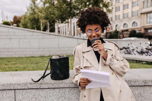 Cheerful brunette woman in stylish beige trench coat drinks coffee outside