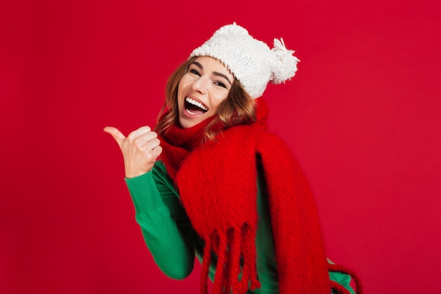 Cheerful brunette woman in sweater, funny hat and scarf