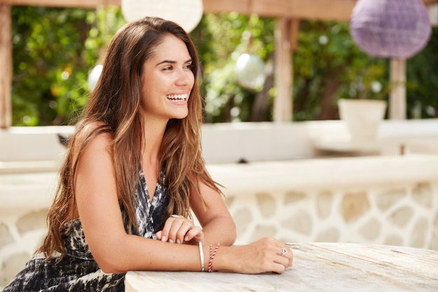 Cheerful brunette woman waits for order in sidewalk cafeteria, looks joyfully into distance, being pleased to have summer rest after hard working year. people, recreation, lifestyle concept.