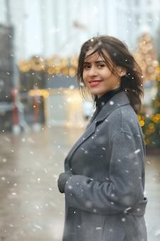 Веселая брюнетка в модном пальто гуляет по городу, украшенному к рождеству, во время снегопада
