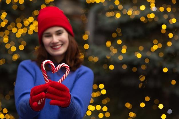 クリスマスツリーでキャンディーと陽気なブルネットの女性。テキスト用のスペース