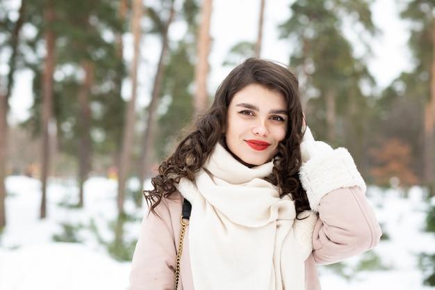 長い髪の陽気なブルネットの女性は冬にコートを着ています。テキスト用のスペース