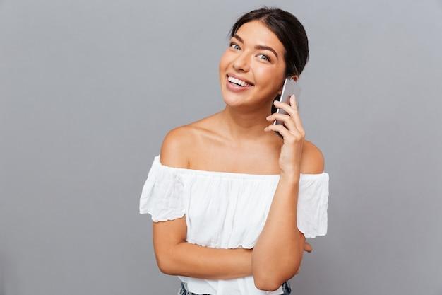 회색 벽에 격리된 전화 통화를 하는 쾌활한 갈색 머리의 젊은 여성