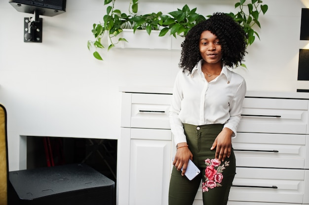 Cheerful business african american lady with afro hair, wear white blouse and green pants posed in cafe with mobile phone at hand.