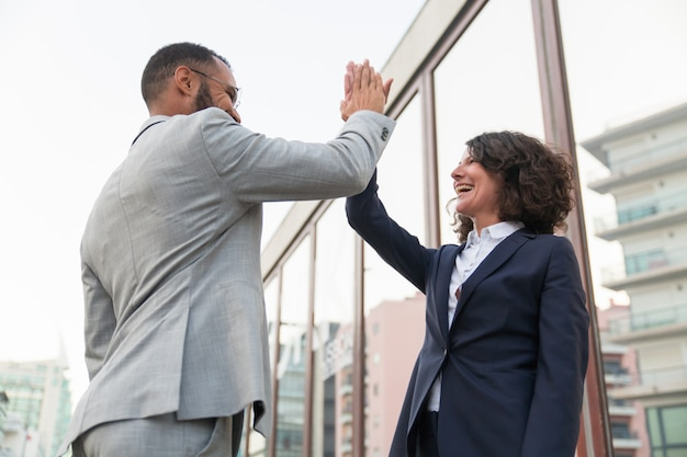 Cheerful business colleagues giving high five