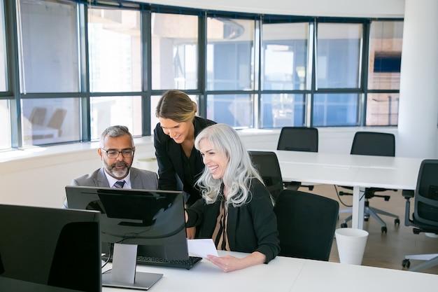 Веселая бизнес-группа смотрит презентацию и смеется. менеджеры сидят на рабочем месте вместе, глядя на монитор компьютера и смеясь. деловое общение или концепция совместной работы