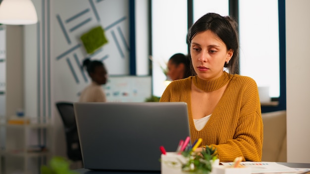 Cheerful business lady typing on laptop computer and smiling sitting at desk in busy start up office enjoying work in creative workplace. diverse team analyzes statistics data in modern company