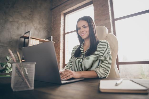 Веселая бизнес-леди печатает нетбук в офисе