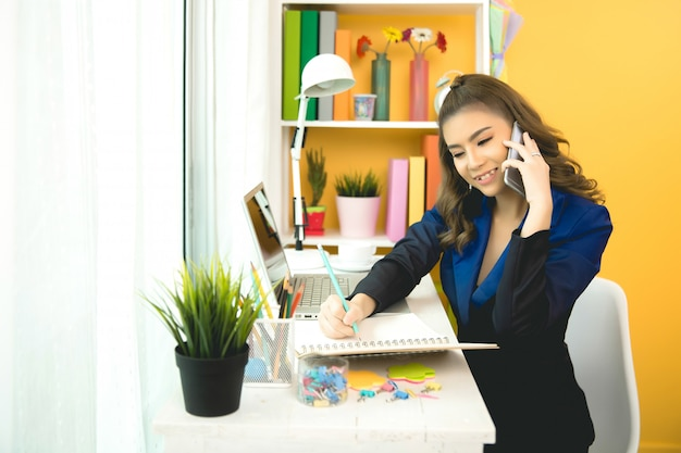 Cheerful business lady working on laptop in office