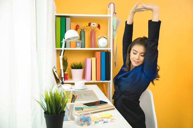 Веселый бизнес-леди работает на ноутбуке в офисе