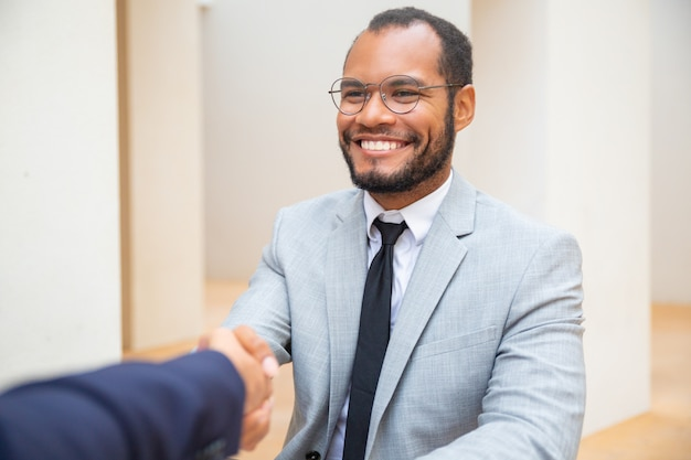 Cheerful business man greeting colleague