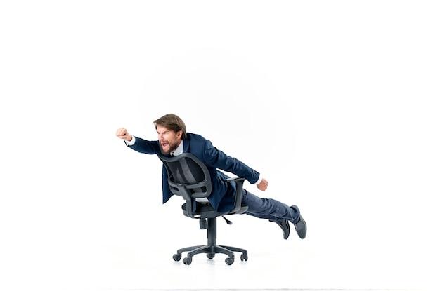 スーツを着た陽気なビジネスマンがオフィスマネージャーの椅子に転がっています。高品質の写真