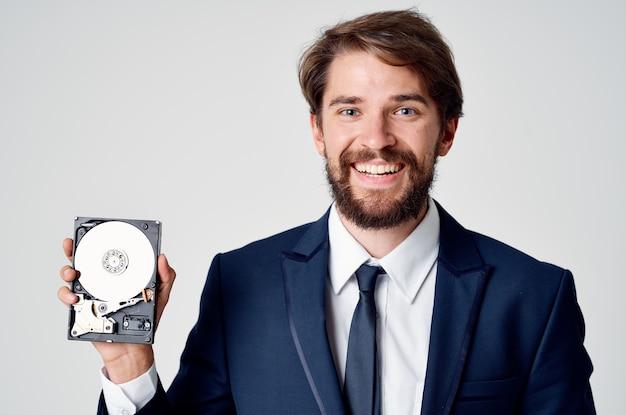 Веселый деловой человек с жестким диском от защиты данных компьютера