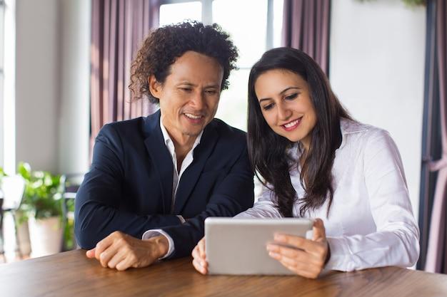 Веселые деловые люди обсуждают данные на планшете