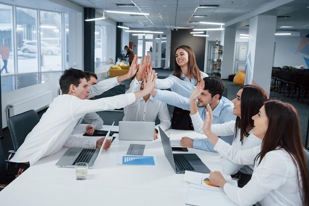 Веселые деловые люди. работа сделана. группа офисных работников с удовольствием бьет свои рекорды и добивается успеха