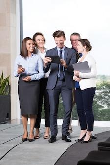 Cheerful business people looking at digital tablet
