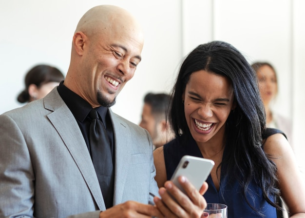 Cheerful business people using a mobile phone