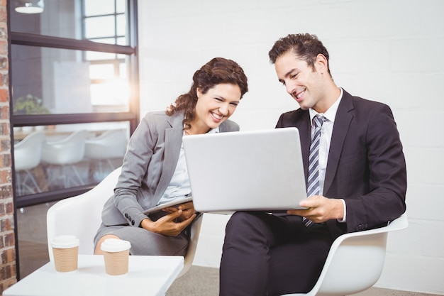 Cheerful business people using technology