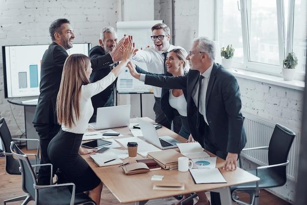 現代のオフィスで働きながら成功するためにお互いにハイタッチを与える陽気なビジネスチーム