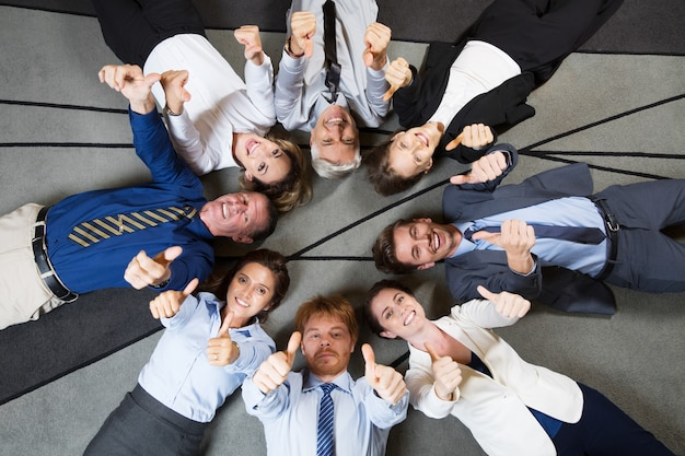 Cheerful business team showing thumbs up on floor