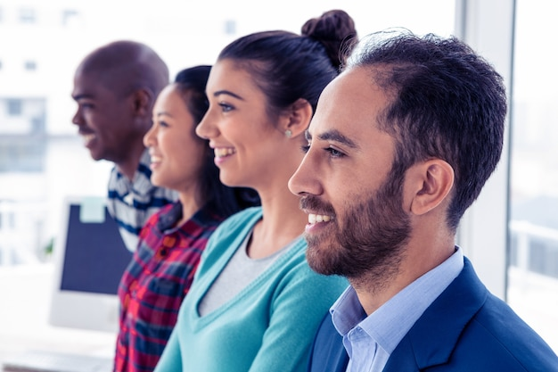 Cheerful business team standing in row at creative office