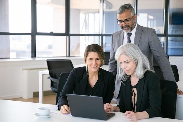 ノートパソコンでプレゼンテーションを見たり、職場に座ったり、ディスプレイを見つめたり、笑顔を見せたりする陽気なビジネスチーム。スペースをコピーします。ビジネス会議のコンセプト