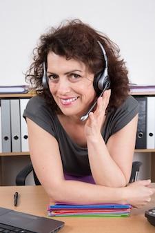 Веселая деловая женщина в офисе, улыбаясь в колл-центр