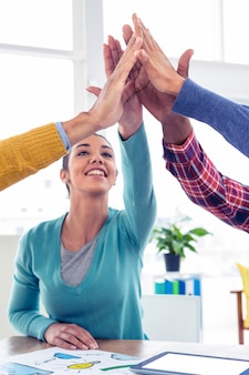 Cheerful business woman doing high five with team in creative office