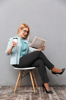 Cheerful business woman drinking coffee reading newspaper.