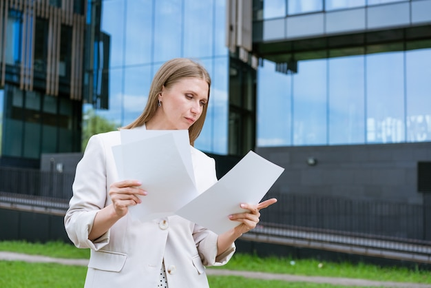 Cheerful business woman holding folder smiling middle aged businesswoman in formal attire holding do...