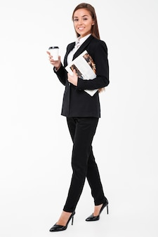 Cheerful business woman holding newspaper drinking coffee.