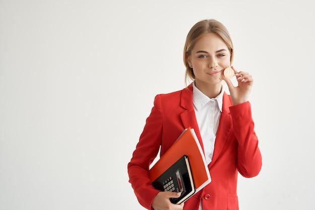 赤いジャケットコイン暗号通貨電子マネーで陽気なビジネス女性