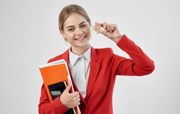 赤いジャケットの暗号通貨ビットコイン電子マネーで陽気なビジネスウーマン。高品質の写真