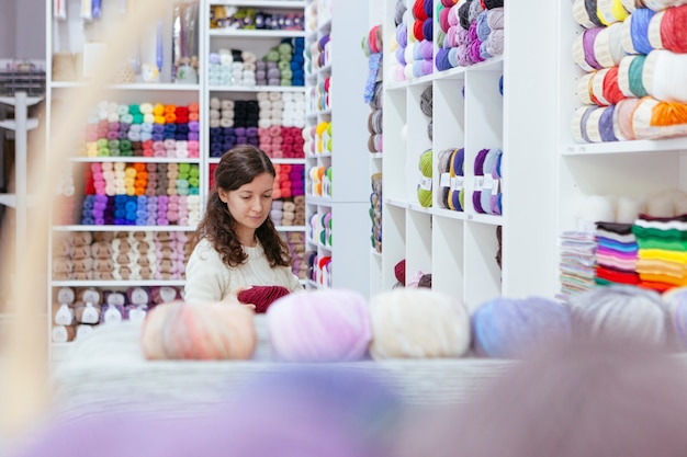 Cheerful business woman organizing wool yarns at her own retail shop