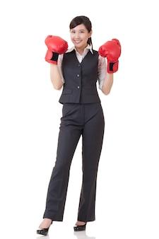 Веселая бизнес-леди поднимает руки с красными боксерскими перчатками, портрет в полный рост изолировал один белый фон.