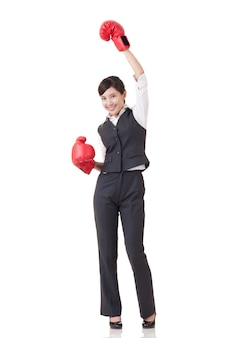 Cheerful business woman raise up hands with red boxing gloves, full length portrait isolated one white background.